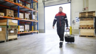 A Linde Material Handling technician walking through a warehouse