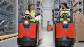 Two employees drive N20 series order pickers from Linde Material Handling in the warehouse.