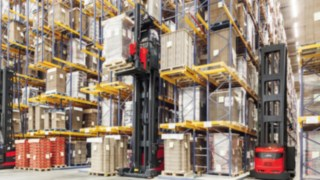 Two Linde Material Handling very narrow aisle trucks in use in a high shelving warehouse.