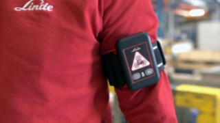 The Distance Beeper from Linde on the arm of an employee