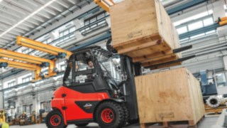 Electric forklift truck transporting heavy crates