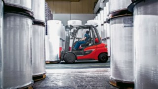 Linde forklift truck driving between rolls of paper
