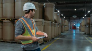 Warehouse worker wearing an interactive warning vest from Linde Material Handling in a poorly lit warehouse