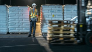 Warehouse worker and forklift truck cross paths; the warehouse worker is easily seen thanks to the interactive warning vest from Linde Material Handling