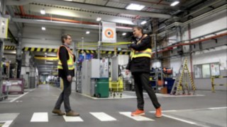 Two factory workers with the Linde Secure Distance Vest approach each other at a safe distance