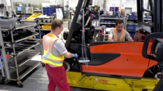 Two employees in production keep a safe distance thanks to the Distance Vest from Linde
