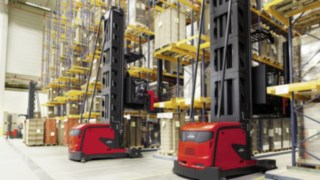 Two narrow-aisle K trucks from Linde Material Handling driving amongst high shelving