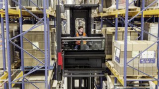 Driver in the cab of a narrow-aisle K truck from Linde Material Handling amongst high shelving