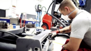 Individual components of the used forklift are overhauled and cleaned by an employee.