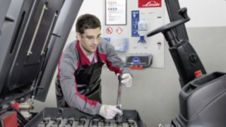 A service technician checks the drive battery of a Linde used forklift