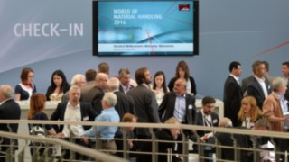 Check-in desk with people at the World of Material Handling fair in 2016