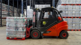 A hired V-forklift from Linde transports a pallet of water boxes from Agua Mineral in the warehouseLager