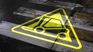 The Safety Guard stationary warning projector from Linde Material Handling projects a yellow warning signal onto the floor.