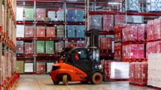 A forklift truck by Linde Material Handling picks up pallets of drinks boxes in the French plant of Coca-Cola European Partners France.