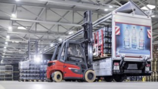Linde X35 electric forklift truck loads a loading truck with crates of drinks from Ensinger