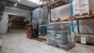 An employee of Reinheim-based Grass GmbH working in the warehouse with a Linde Material Handling pallet stacker