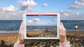 The Virtual Showroom app from Linde Material Handling projects an industrial truck onto the surrounding beach on the tablet screen.
