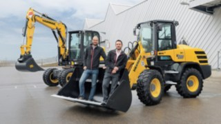 Dominik Haag and Markus Köhler from Yanmar Compact Equipment Europe standing in the bucket of an excavator.