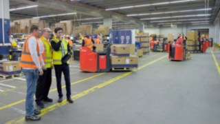 Three people analyse the occurrences in a factory building.