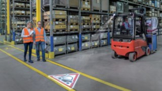 Two people walk in the warehouse and cross paths with a forklift truck