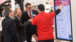 A Linde employee demonstrates the Linde Truck Call App to visitors at LogiMAT 2019.